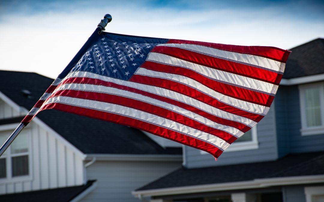 American flag flying over a neighborhood.